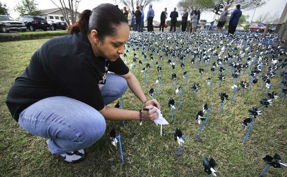 Rachel Ojeda, aunt of Josiah Williams, writes his name on one of 19 white pinwheels symbolizing children who died from abuse in Bexar County in 2012. Photo: Bob Owen / San Antonio Express-News