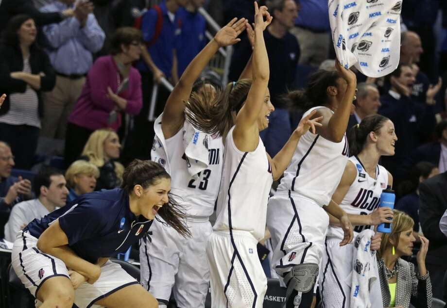 CORRECTS TO STEFANIE DOLSON- Connecticut forward Stefanie Dolson, left, celebrates with her teammates in the final seconds of the second half of a women's NCAA regional final basketball game against Kentucky in Bridgeport, Conn., Monday, April 1, 2013. Connecticut won 83-53 and advances to the Final Four. (AP Photo/Charles Krupa)