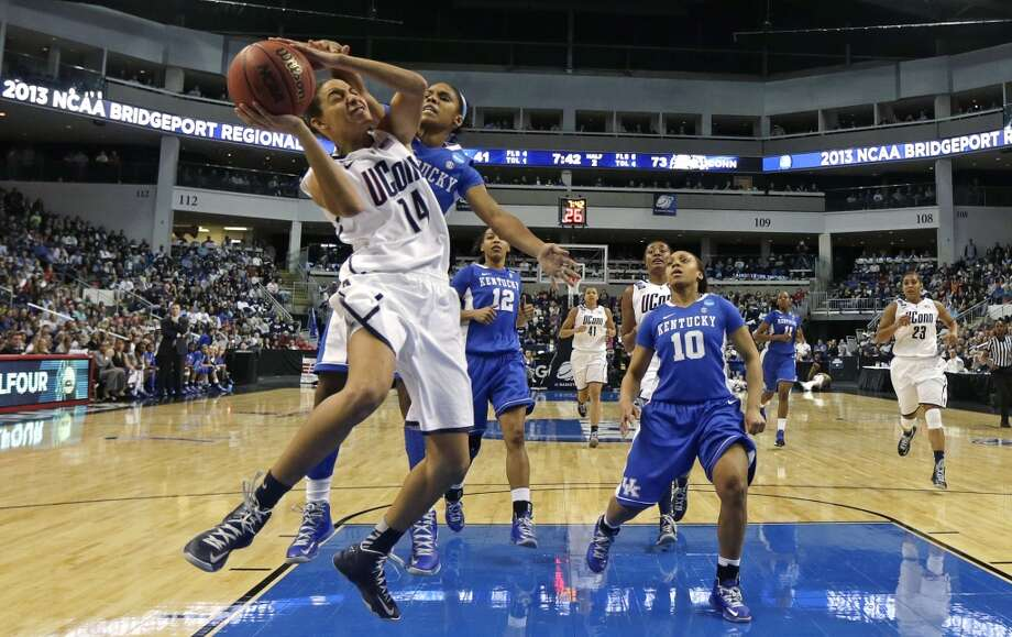 Connecticut guard Bria Hartley (14) tries to break free from Kentucky guard Janee Thompson, rear, on a drive to the basket in the second half of a women's NCAA regional final basketball game in Bridgeport, Conn., Monday, April 1, 2013. Connecticut won 83-53 and advances to the Final Four. (AP Photo/Charles Krupa)