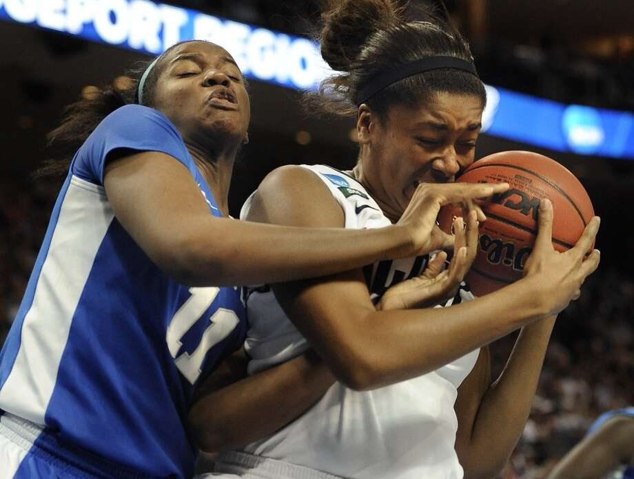Kentucky's DeNesha Stallworth, left, tangles with Connecticut's Morgan Tuck, right, during the second half of a women's regional final game in the NCAA college basketball tournament in Bridgeport, Conn., Monday, April 1, 2013. Connecticut won 83-53.(AP Photo/Jessica Hill)