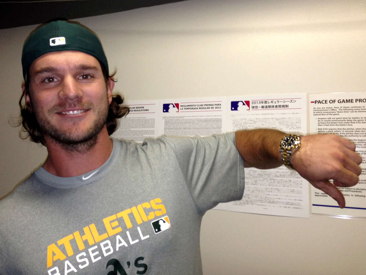 Oakland Athletics catcher John Jaso, a former Seattle Mariners catcher, poses for a photo with his new Rolex watch, a thank you gift from Mariners' Felix Hernandez for catching his perfect game in August, on Monday, April 1, 2013, in Oakland, Calif. A clubhouse employee delivered the gold watch from Seattle's side to the Oakland clubhouse for Jaso about 90 minutes before first pitch in the Mariners-Athletics season opener baseball game Monday night.