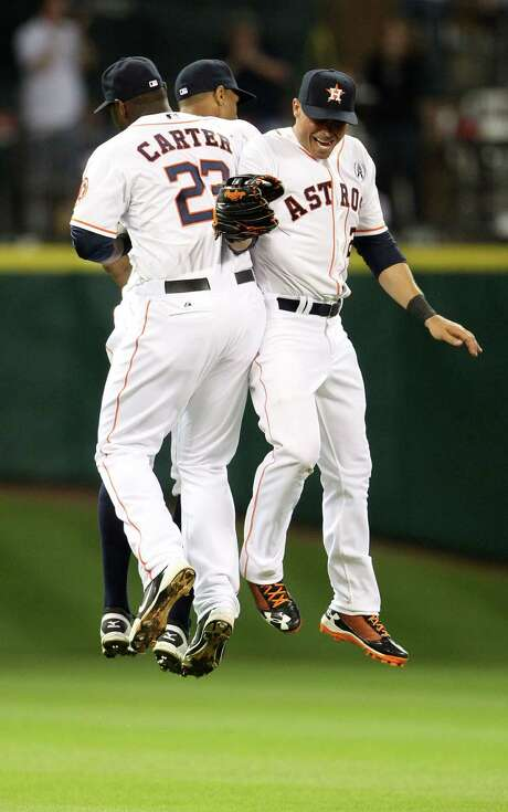 Rick Ankiel, right, may be one of the oldest Astros at 33, but there was plenty of spring in his step as he enjoyed Sunday's opening-night win with Chris Carter (23) and Justin Maxwell. Photo: Karen Warren, Staff / © 2013 Houston Chronicle