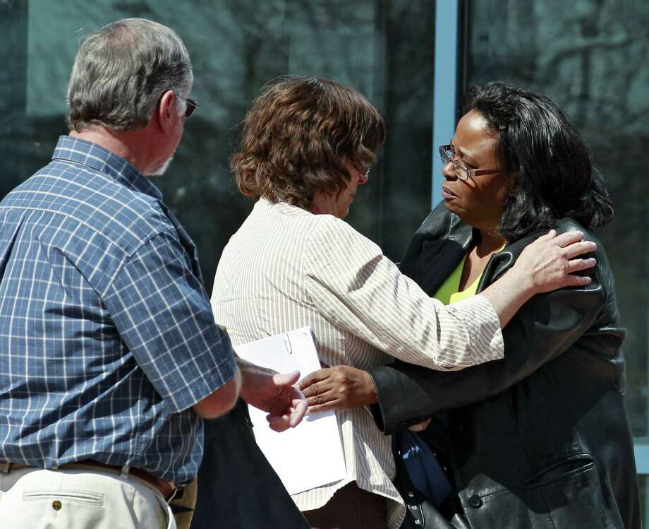 Sherry Delaney (right) hugs Arlene Holmes, the mother of James Holmes, as his father, Robert, watches after leaving the hearing in Centennial, Colo. Prosecutors will seek the death penalty. Photo: Brennan Linsley / Associated Press