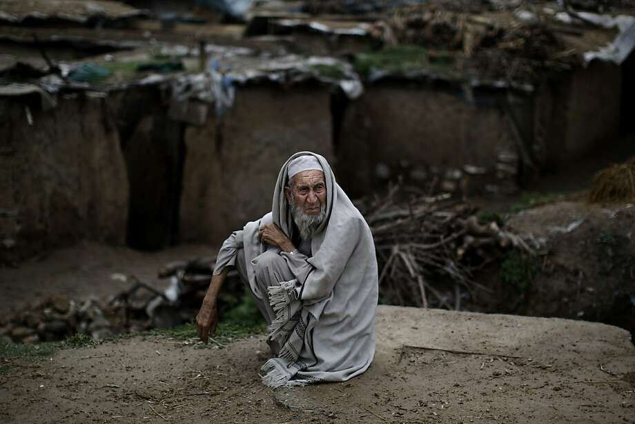 Pakistani Wazeer Khan, 87, sits on a roadside near his home, on the outskirts of Islamabad, Pakistan, Monday, April 1, 2013. Khan and his family fled Pakistan's tribal area of Bajur in 2009, due to fighting between the Taliban and the army, and took refuge in Islamabad. Photo: Muhammed Muheisen, Associated Press