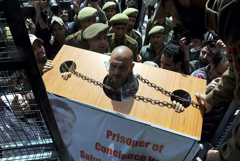 Indian police officials detain Mohammad Ahsan Untoo, a human rights activist wearing a symbolic device to protest against illegal detention of political activists in in Indian-administered Kashmir on April 1, 2013. Many separatist political leaders and activists have recently been detained by police to prevent them from organising protests in demand of returning mortal remains of a Kashmiri Muslim Mohammad Afzal Guru who was executed and buried in a high security prison in Delhi on February 9, 2013 after being convicted for his role in a deadly attack on India's parliament in 2001.  Photo: Rouf Bhat, AFP/Getty Images
