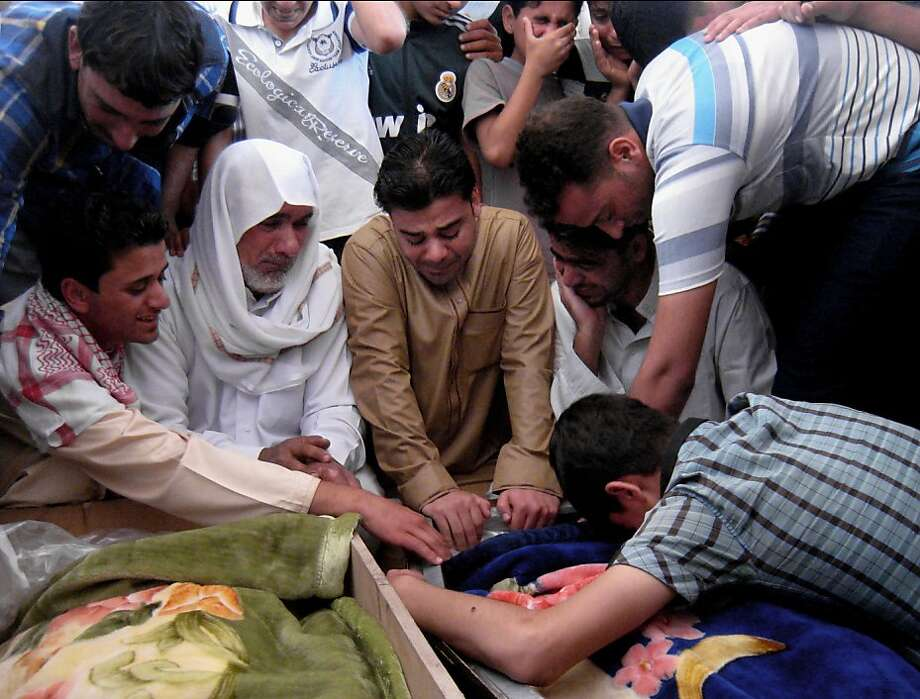 Mourners grieve over the bodies of three men killed on Sunday, March 31, 2013 during a mass funeral in Fallujah, 40 miles (65 kilometers) west of Baghdad, Iraq, Monday, April 1, 2013. Assailants gunned down Sheikh Talib Youssef, a mosque preacher, along with his nephew Othman Khalil and another man on Sunday, residents say Sheikh Talib Youssef was one of the organizers of weekly Sunni demonstrations against the Shiite-led government that have been taking place for the past three months.  Photo: Bilal Fawzi, Associated Press