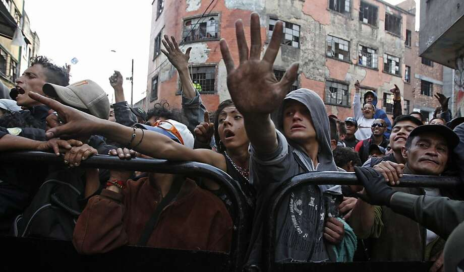 "Homeless and drug users wave behind a security barrier to Colombian President Juan Manuel Santos, not seen,  as he  makes his first visit ever to the area known as ""Bronx Street"" in Bogota, Colombia,  Monday April 1, 2013. Santos described the notorious and dangerous neighborhood, mostly populated by drug users, drug dealers and homeless,  as ""a factory of evil"" and saluted a campaign  by the local Bogota government to clean up the widespread drug dealing and other crime in the area.  Photo: Fernando Vergara, Associated Press"