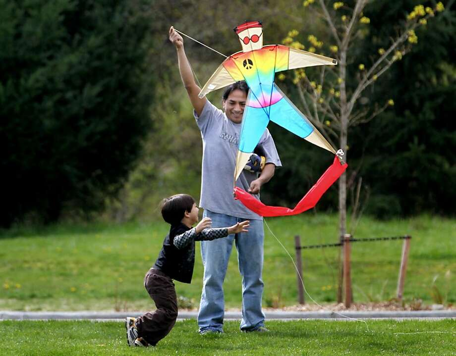 Taking advantage of a steady breeze and comfortable temperatures Cesar Cachinguango and his 3 1/2 year-old son Indie enjoy an afternoon of kite flying at Woodland Creek Community Park, Monday, April 1, 2013 in Lacey,Wash.  Photo: Steve Bloom, Associated Press