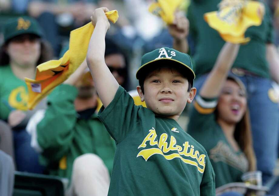OAKLAND, CA - APRIL 01:  An Oakland Athletics fan cheers for the Athletics during a pregame ceremony before their game against the Seattle Mariners  on Opening Day at O.co Coliseum on April 1, 2013 in Oakland, California. Photo: Ezra Shaw, Getty Images / 2013 Getty Images