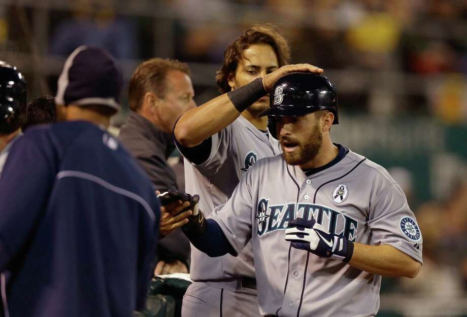 OAKLAND, CA - APRIL 01: Dustin Ackley #13 of the Seattle Mariners is congratulated by teammates after he scored on a single by Franklin Gutierrez #21 in the fifth inning of their game against the Oakland Athletics during Opening Day at O.co Coliseum on April 1, 2013 in Oakland, California. Photo: Ezra Shaw, Getty Images / 2013 Getty Images