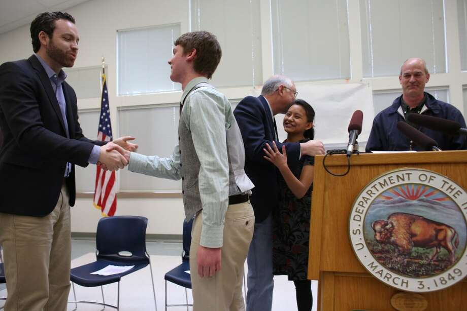 BLM Deputy Director Neil Kornze, left, shakes hands Graham Crawbuck, 16, of Friday Harbor as Secretary of the Interior Ken Salazar embraces Reyna Ellis, 17, of Friday Harbor and Rep. Rick Larsen looks on, right as the newly-designated San Juan Islands National Monument is celebrated on Monday, April 1, 2013 at the senior center in Anacortes. (Joshua Trujillo, seattlepi.com)
