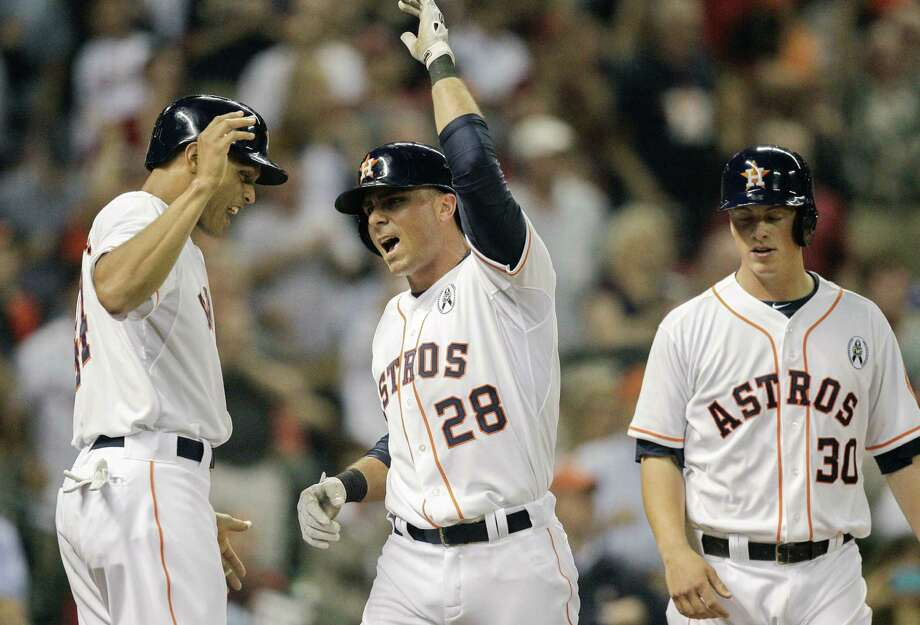 Rick Ankiel (center) got his teammates buzzing Sunday with a homer that helped Houston to a win. Photo: Bob Levey / Getty Images