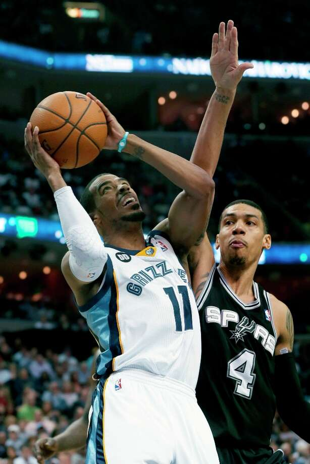 Memphis Grizzlies' Mike Conley (11) shoots in front of the Spurs' Danny Green (4) during the first half in Memphis, Tenn., Monday, April 1, 2013. Conley scored 23 points in the Grizzlies 92-90 victory over the Spurs. Photo: Danny Johnston, Associated Press / AP