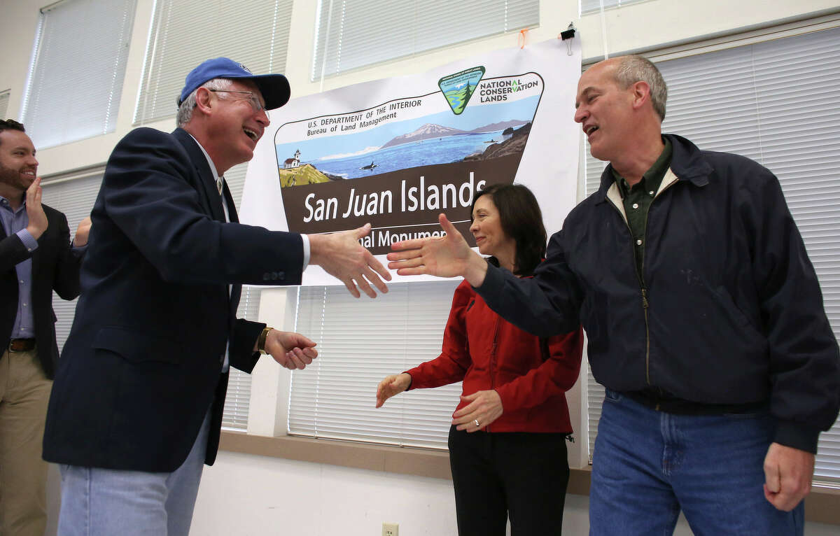 Secretary of the Interior Ken Salazar, left, shakes hands with Rep. Rick Larsen and Senator Maria Cantwell, rear, celebrates with Neil Kornze of the BLM as the newly-designated San Juan Islands National Monument is celebrated on Monday, April 1, 2013 at the senior center in Anacortes.