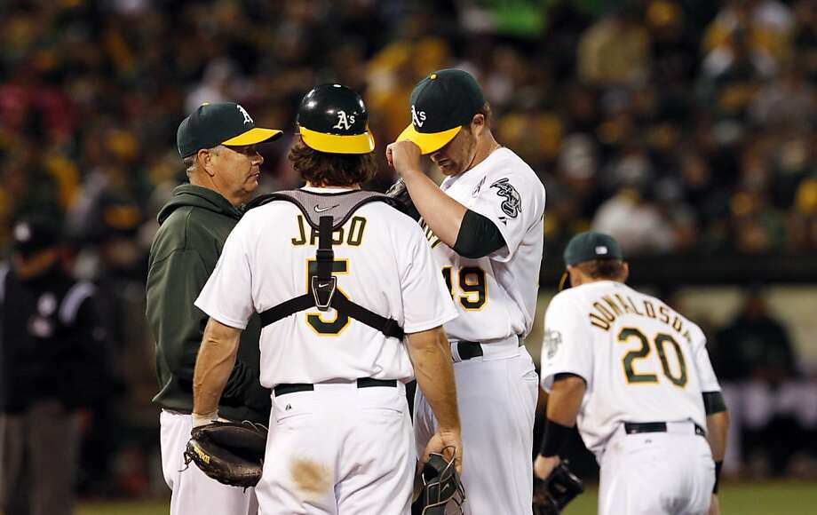 Pitching coach Curt Young (left), an A's pitcher in the 1980s, counsels catcher John Jaso and pitcher Brett Anderson. Photo: Carlos Avila Gonzalez, The Chronicle