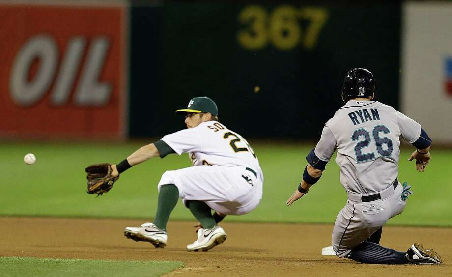 Seattle Mariners' Brendan Ryan (26) steals second base past Oakland Athletics' Eric Sogard, left, in the seventh inning of a baseball game Monday, April 1, 2013, in Oakland, Calif. Photo: AP