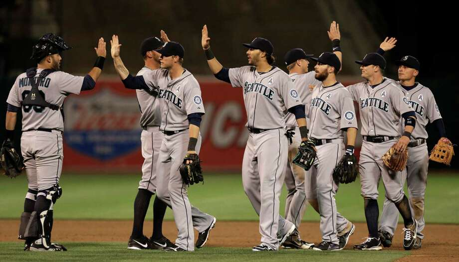 The Seattle Mariners celebrate their win over the Oakland Athletics at the end of a baseball game Monday, April 1, 2013, in Oakland, Calif. Photo: AP