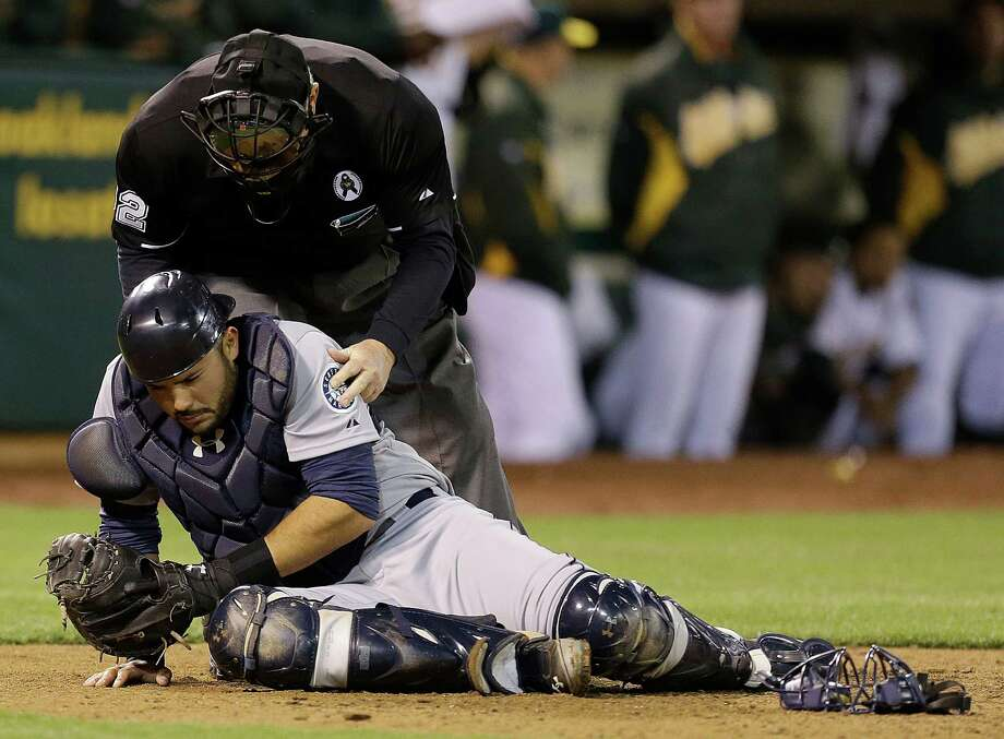 Home plate umpire Dana DeMuth checks on the condition of Seattle Mariners catcher Jesus Montero, who was hit by a foul tip by Oakland Athletics' Yoenis Cespedes in the ninth inning of a baseball game Monday, April 1, 2013, in Oakland, Calif. Photo: AP