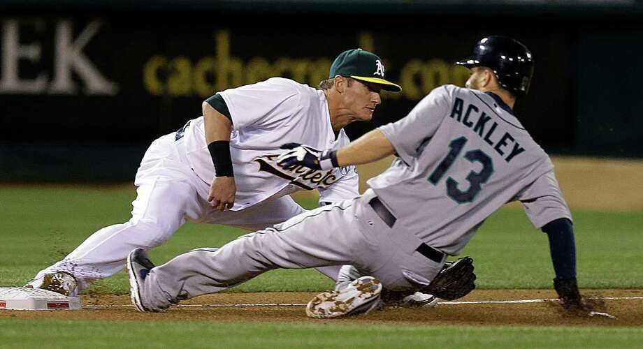 Seattle Mariners' Dustin Ackley (13) slides under the tag of Oakland Athletics third baseman Josh Donaldson, left, in the fifth inning of a baseball game Monday, April 1, 2013, in Oakland, Calif. Ackley advanced to third base on a single hit by  Mariners' Brendan Ryan. Photo: AP