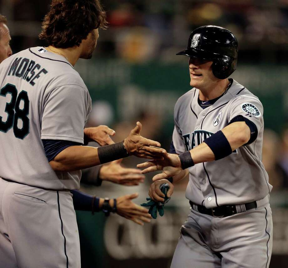 Seattle Mariners' Brendan Ryan, right, is congratulated by Michael Morse (38) after Ryan scored on a single by Franklin Gutierrez in the fifth inning of a baseball game against the Oakland Athletics Monday, April 1, 2013, in Oakland, Calif. Photo: AP