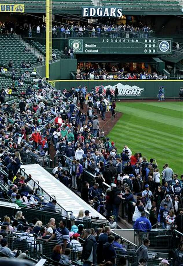 Fans walk the warning track as they attend an open house at Safeco Field Monday, April 1, 2013, in Seattle. The Seattle Mariners opened the gates of the ballpark to let fans see changes and enhancements to the field and to watch the season opener baseball game against the Athletics being played in Oakland, Calif. on the park's giant new video screen. Photo: Ted S. Warren, AP / AP
