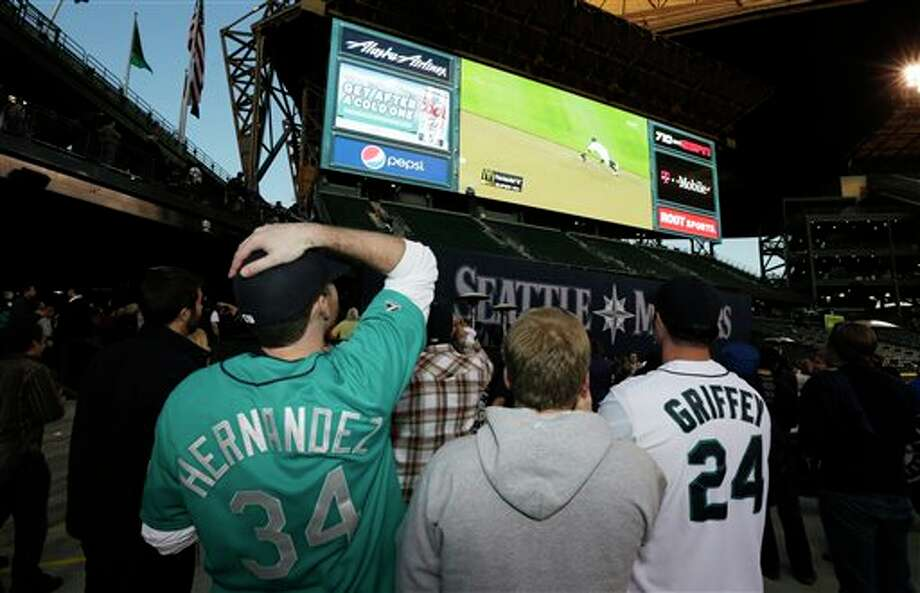 Seattle Mariner fan Brian Bull, left,  reacts to a play shown on the new video screen at Safeco Field in Seattle, Monday, April 1, 2013. The Mariners held an open house game-viewing party at the ballpark to show the season opener baseball game against the Athletics being played in Oakland, Calif. Photo: Ted S. Warren, AP / AP