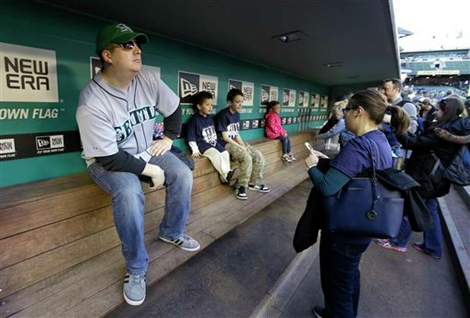 Shane Kalles, left, strikes a baseball manager pose as he checks out the visitors dugout at Safeco Field Monday, April 1, 2013, in Seattle. The Mariners held an open house game-viewing party at the ballpark to watch the season opener  baseball game against the Athletics being played in Oakland, Calif. on the park's giant new video screen and to let fans check out improvements at the ballpark. Photo: Ted S. Warren, AP / AP