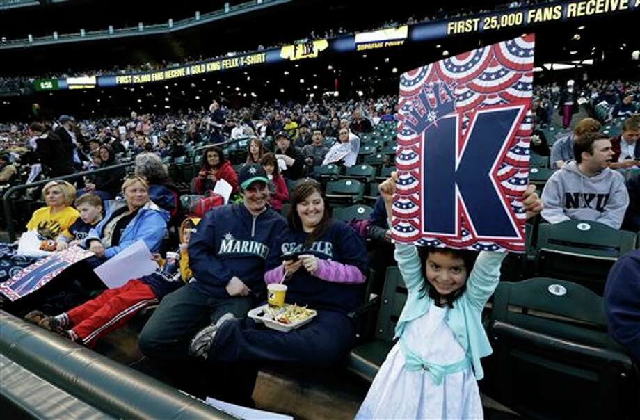 "Sofia Meza, 6, holds up a ""K-Card"" in support of Seattle Mariners pitcher Felix Hernandez as she attends an open house game-viewing party at Safeco Field Monday, April 1, 2013, in Seattle. The Seattle Mariners opened the gates of the ballpark to let fans see changes and enhancements to the field and to watch the season opener  baseball game against the Athletics being played in Oakland, Calif. on the park's giant new video screen. Photo: Ted S. Warren, AP / AP"