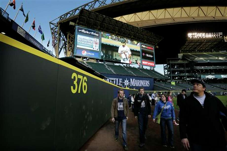Fans check out the 376 distance marker for the now-closer left-field wall at Safeco Field Monday, April 1, 2013, in Seattle. The Mariners held an open house game-viewing party at the ballpark to let fans watch the season opener MLB baseball game against the Athletics being played in Oakland, Calif. on the park's giant new video screen at upper left. Photo: Ted S. Warren, AP / AP