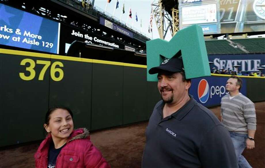 "Eric Nemeth, the man who invented and sold the original foam ""M"" Seattle Mariners headgear back in 2000 and 2001, wears one of his original models as he checks out the 376 distance marker for the now-closer left-field wall at Safeco Field Monday, April 1, 2013, in Seattle. The Mariners held an open house game-viewing party at the ballpark to let fans watch the season opener MLB baseball game against the Athletics being played in Oakland, Calif. Nemeth said that if the team does well this season, he might just bring back the M's for sale again. Photo: Ted S. Warren, AP / AP"