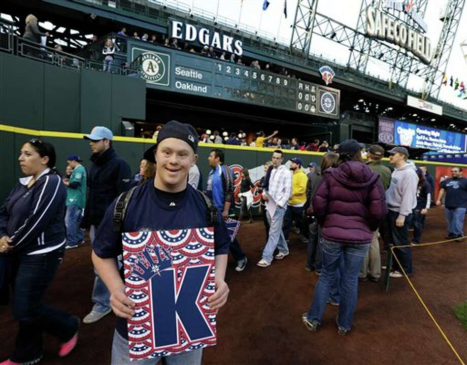 "Kristian Enge, left, of Seattle, holds a ""K-Card"" in support of Seattle Mariners pitcher Felix Hernandez as he attends an open house game-viewing party at Safeco Field Monday, April 1, 2013, in Seattle. The Seattle Mariners opened the gates of the ballpark to let fans see changes and enhancements to the field and to watch the season opener MLB baseball game against the Athletics being played in Oakland, Calif. on the park's giant new video screen. Photo: Ted S. Warren, AP / AP"