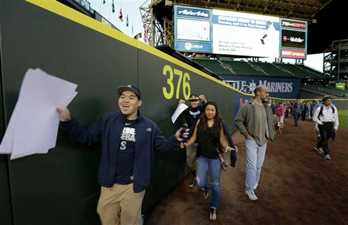 Fans cheer as they pass the new distance marker for the now-closer left-field wall at Safeco Field Monday, April 1, 2013, in Seattle. The Mariners held an open house game-viewing party at the ballpark to allow fans to watch the season opener baseball game against the Athletics being played in Oakland, Calif. on the park's giant new video screen and check out park improvements such as a new closer left-field wall.