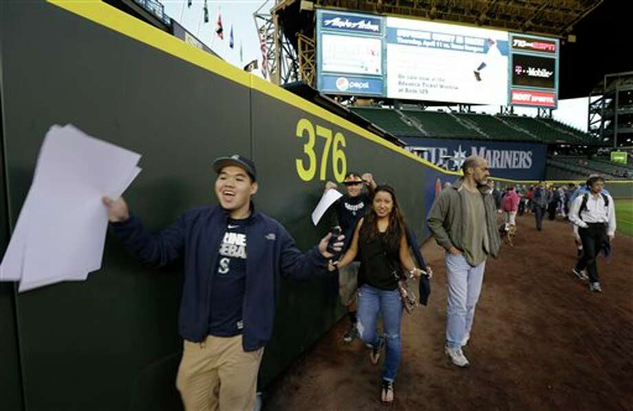 Fans cheer as they pass the new distance marker for the now-closer left-field wall at Safeco Field Monday, April 1, 2013, in Seattle. The Mariners held an open house game-viewing party at the ballpark to allow fans to watch the season opener  baseball game against the Athletics being played in Oakland, Calif. on the park's giant new video screen and check out park improvements such as a new closer left-field wall. Photo: Ted S. Warren, AP / AP