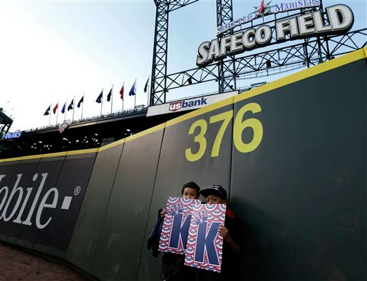 Cash Wilmot-Collins, left, 10, and his friend Miles Frazer, 9, right, pose for a family photo under the new distance marker for the now-closer leftfield wall at Safeco Field Monday, April 1, 2013, in Seattle. The boys were attending an open house game-viewing party at the ballpark to watch the season opener baseball game against the Athletics being played in Oakland, Calif. on the park's giant new video screen.