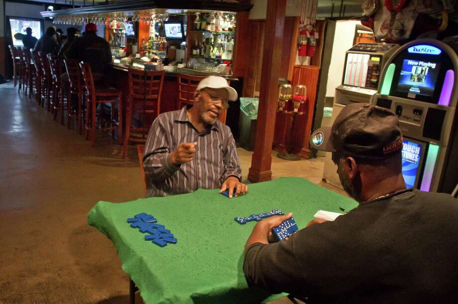 Play dominoes (like these patrons at Sam Jordan's Bar). Photo: John Storey, Special To The Chronicle / SFC
