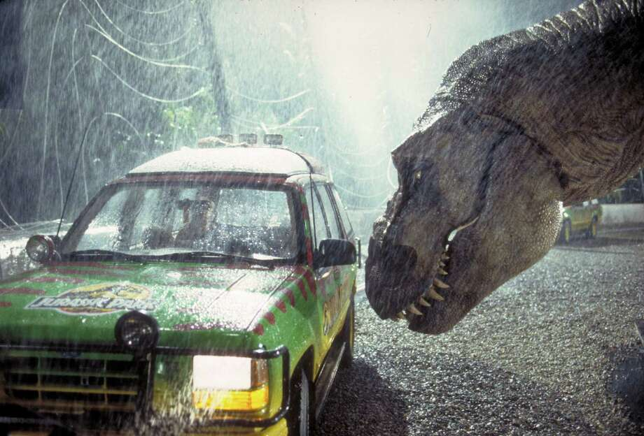 A Tyrannosaurus Rex menaces a truck in a scene from the film 'Jurassic Park.' Photo: Murray Close, Getty Images / 2011 Murray Close