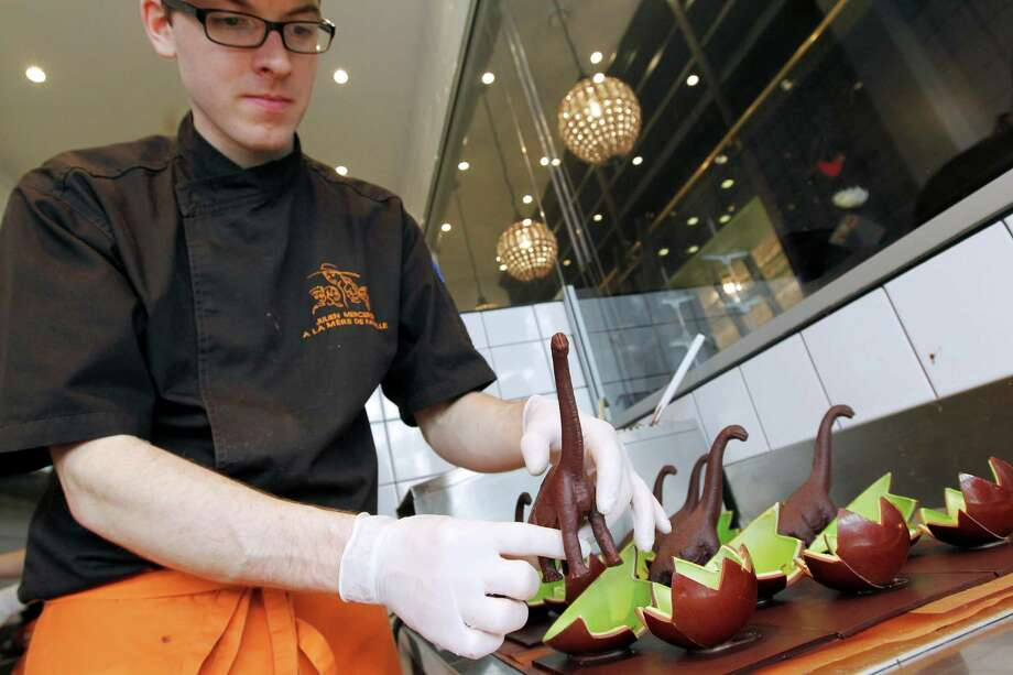 An employee displays chocolate dinosaur-shaped and Easter eggs in the chocolate confectioner 'La Mere de famille' on April 20, 2011 in Paris. This fancy Easter chocolate edition is entitled 'Jurassic Paques,' a play on words referring to 'Jurassic Park' and meaning in French 'Jurassic Easter.' Photo: AFP/Getty Images