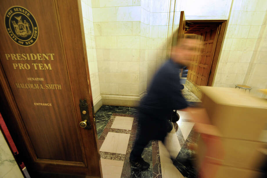 A state OGS worker moves boxes from Sen. Malcolm Smith's former office as president pro tempore of the state Senate on December 29, 2010, after a power change after elections.  Photo: Skip Dickstein, TIMES UNION