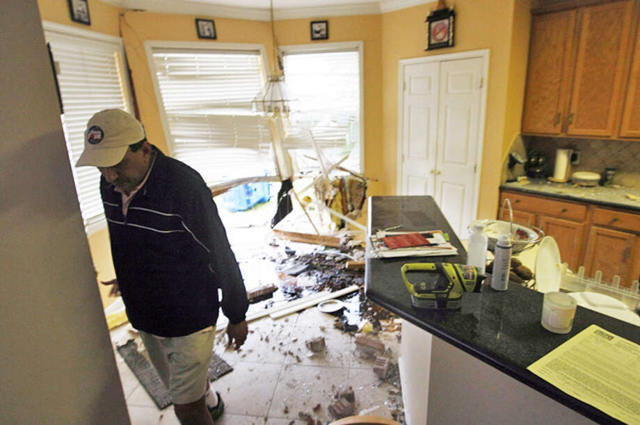 Mukesh Dhanani inspects the damage after a driver slammed into his home about 2 a.m. Tuesday in the 19300 block of Shiloh Creek Lane near Savannah Pines Drive. (Johnny Hanson / Houston Chronicle) Photo: .