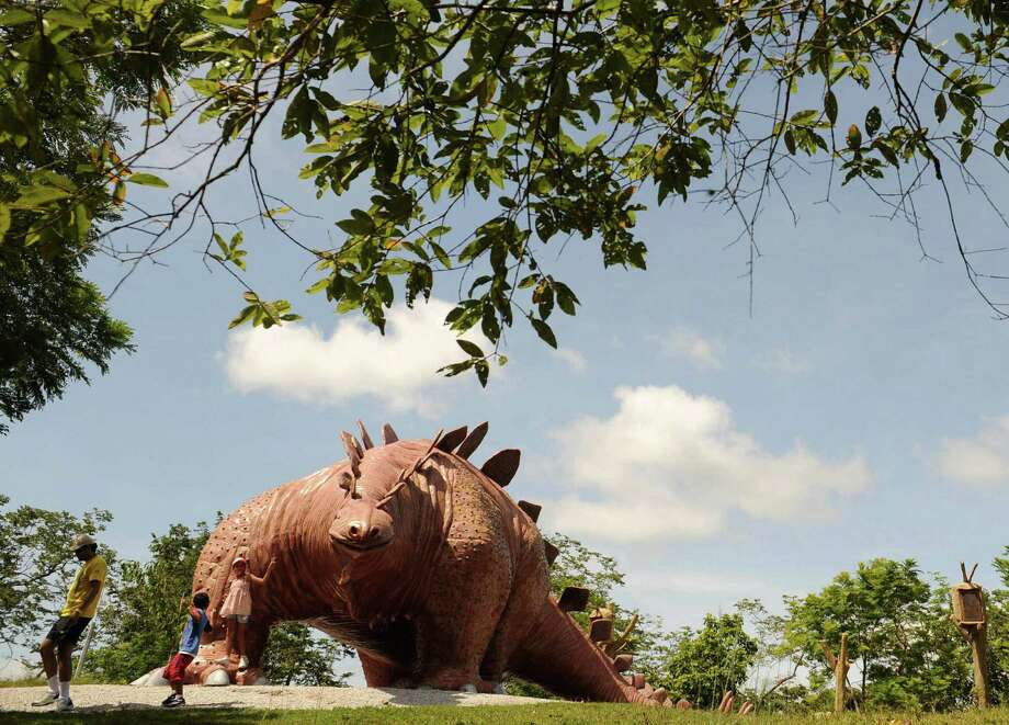Two children play in the Jurassic Park, at the Napoles ranch theme park in Puerto Triunfo, Colombia on June 21, 2009. Photo: AFP/Getty Images