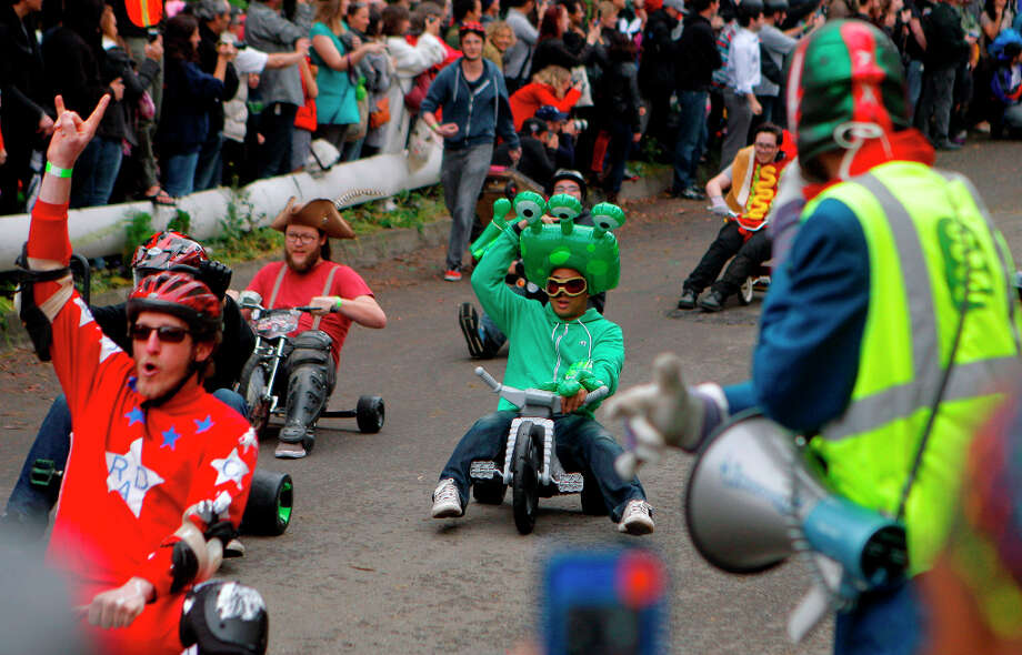 Bring Your Own Big Wheel racers heading down Vermont street on March 31st, 2013 in San Francisco, Calif. Bring Your Own Big Wheel 2013 (BYOBW) is an Easter Sunday event where participants risk humiliation and serious injury racing their big wheels down the crazy curvy Vermont & 20th streets. Photo: Jessica Olthof, The Chronicle / ONLINE_YES