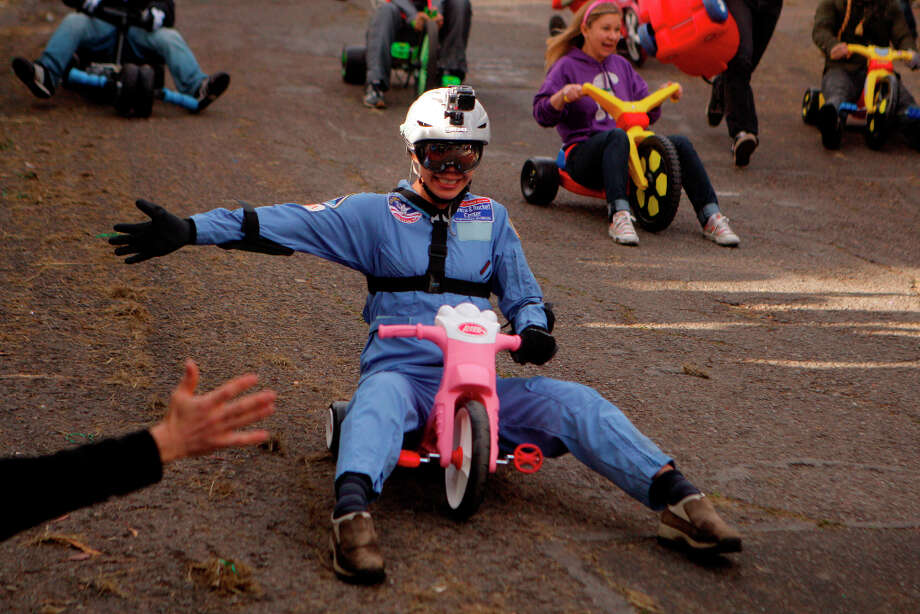 Bring Your Own Big Wheel racer gives a high five as she heads to the finish line on Vermont street on March 31st, 2013 in San Francisco, Calif. Bring Your Own Big Wheel 2013 (BYOBW) is an Easter Sunday event where participants risk humiliation and serious injury racing their big wheels down the crazy curvy Vermont & 20th streets. Photo: Jessica Olthof, The Chronicle / ONLINE_YES