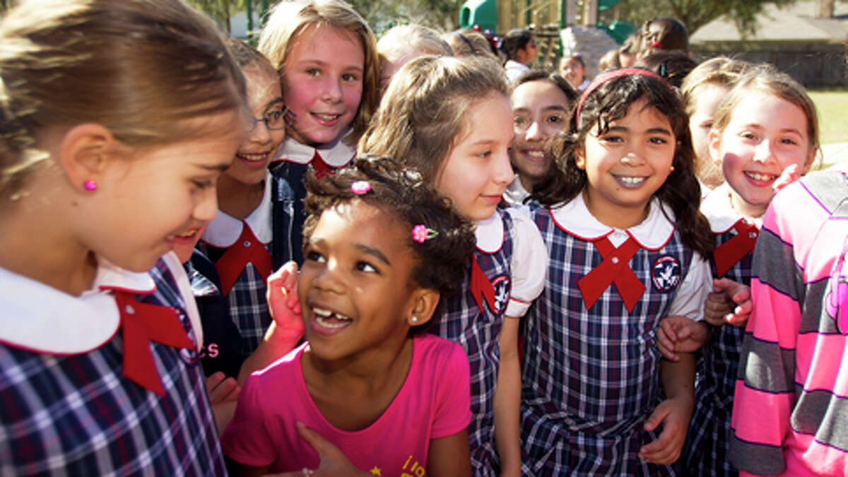 Cuban refugee Ainoa Lara, left, in pink, and her sister, Naydyd Lara, far right, play with a group of 4th grade students at St. Laurence Catholic School Friday, Feb. 15, 2013, in Sugar Land. The fourth graders at the school raised $8,000 to help five families, who are refugees from Cuba, settle into their new lives in the United States.