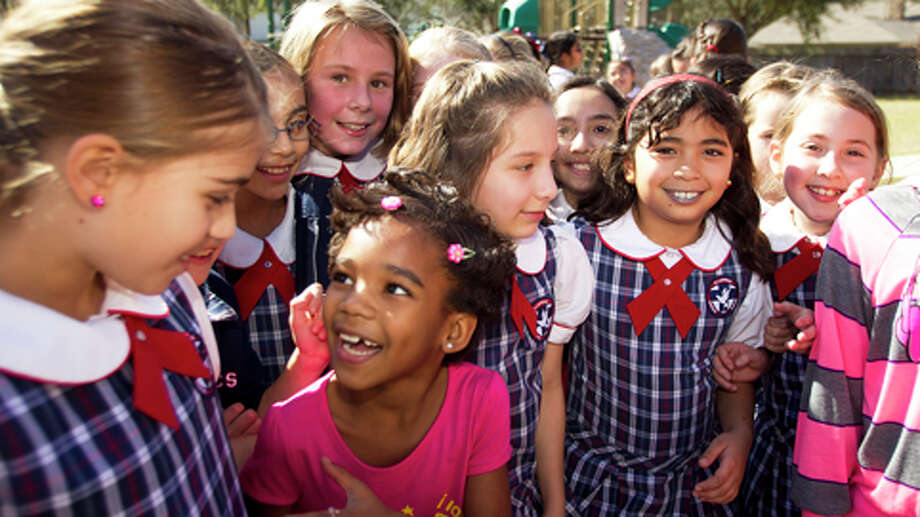 Cuban refugee Ainoa Lara, left, in pink, and her sister, Naydyd Lara, far right, play with a group of 4th grade students at St. Laurence Catholic School Friday, Feb. 15, 2013, in Sugar Land. The fourth graders at the school raised $8,000 to help five families, who are refugees from Cuba, settle into their new lives in the United States. Photo: Brett Coomer, . / © 2013 Houston Chronicle