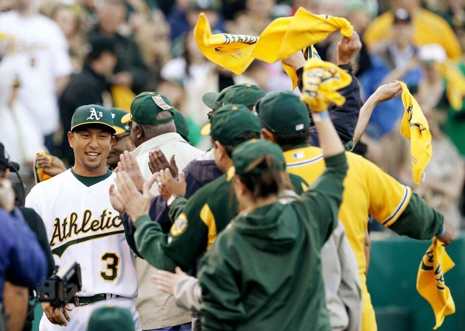 Hiroyuki Nakajima is high fived by fans as he is introduced before the game against the Mariners on Monday. The Oakland Athletics played their 2013 home opener against the Seattle Mariners at O.co Coliseum in Oakland, Calif., on Monday, April 1, 2013. Photo: Carlos Avila Gonzalez, The Chronicle / ONLINE_YES