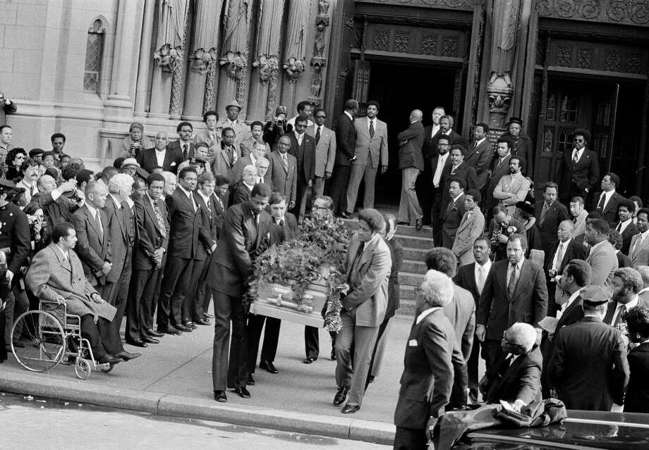 Some of Jackie Robinson's former Brooklyn Dodger teammates carry his casket from Riverside Church in New York, Oct. 27, 1972, following funeral services.  Pallbearers include:  Bill Russell, left, former Boston Celtics basketball star; behind him, ex-Dodger pitcher Ralph Branca; former Dodger pitcher Don Newcombe at right.  In line at left are: former Dodger catcher Roy Campanella, in wheelchair; Chicago Cubs coach Ernie Banks, fourth from left; and Elston Howard, fifth from left, ex-Yankee catcher.  In foreground with white hair is civil rights leader Bayard Rustin.  (AP Photo) Photo: File