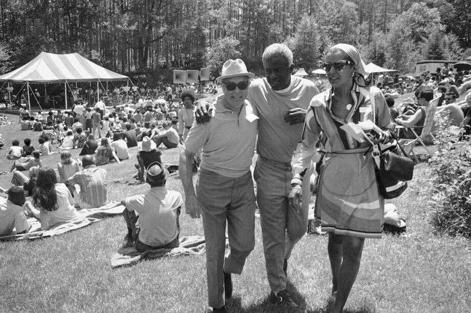 Jackie Robinson, baseball legend, walks with an unidentified friend (left) and Mrs. Arthur Logan, a family friend, at a Jazz Concert at the Robinson home on June 27, 1971 in Stamford, Connecticut. The concert was originally planned by Jackie Robinson Jr., for a drug rehabilitation center. The younger Robinson was killed in an auto accident recently. The Robinsons held the concert for some 2,000 persons. (AP Photo/JW) Photo: JW, File / AP