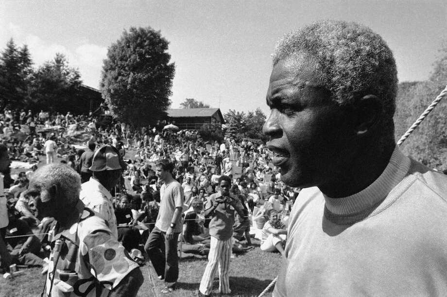 Former Baseball great Jackie Robinson, right, looks over some 2,000 persons assembled on the lawn of his home at Stamford, Connecticut on Sunday, June 27, 1971 before the opening of a Jazz Concert to benefit Daytop Inc., a drug rehabilitation center. The concert was organized by the ex-baseball star�s son, Jackie Jr., a former addict and official at the drug rehabilitation center, who died in an auto accident.   Daytop director Kenneth Williams who spoke before the concert, told the crowd: �I want this to be a memorial for Young Jack.� (AP Photo) Photo: File