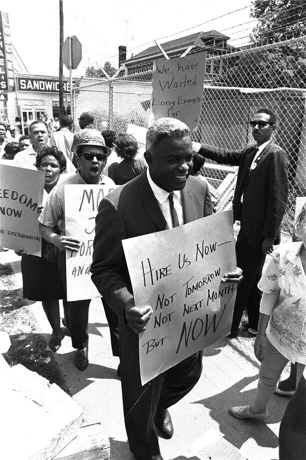 Former baseball star Jackie Robinson carries a placard as he joins pickets at the construction site of the Down State Medical Center in Brooklyn, New York City, August 2, 1963.  Robinson and members of CORE, the Congress of Racial Equality, have been demonstrating in an effort to stop construction of publicly financed projects until more jobs are given to blacks.  (AP Photo) Photo: File / AP1963