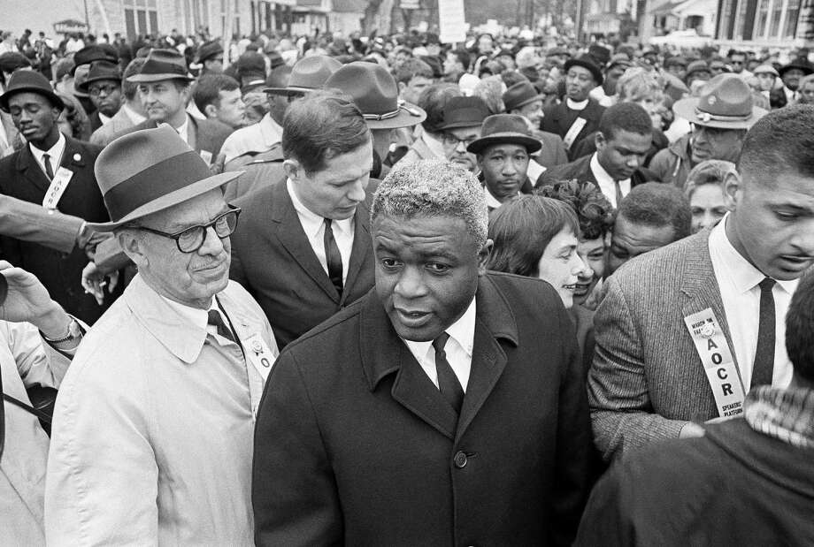 Former baseball star Jackie Robinson, center, joined 10,000 other demonstrators in a march on the capitol in Frankfort, Ky., March 5, 1964. Robinson joined Rev. Martin Luther King in speechmaking following the march. (AP Photo) Photo: Anonymous, File / 1964 AP